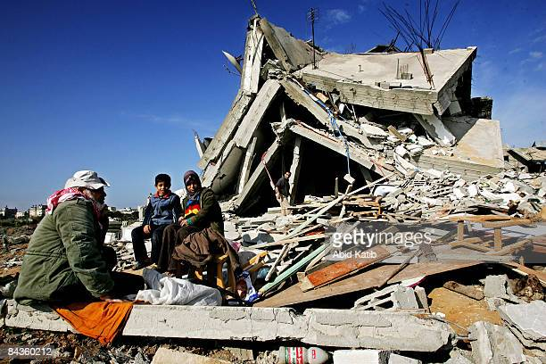 Palestinians sit amongst the rubble of their homes destroyed by Israeli airstrikes on January 19, 2009 in Jabalia, Gaza Strip. While tensions remain...