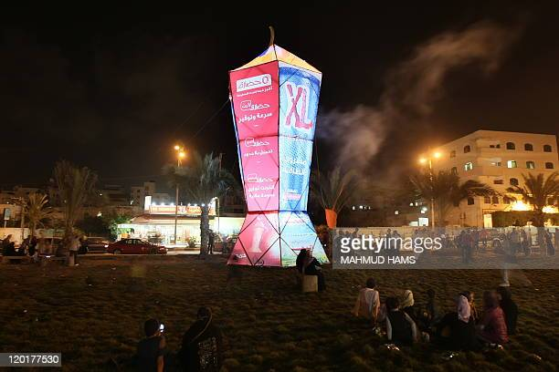 Palestinians sit and walk around a giant lantern set to mark the Muslim holy fasting month of Ramadan on July 31 2011 in Gaza City AFP PHOTO / MAHMUD...