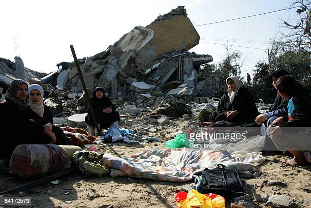 Palestinians sit as they inspect rubble after an Israeli airstrike on January 5 2009 in Rafah southern Gaza Israel is intensifying its widescale...