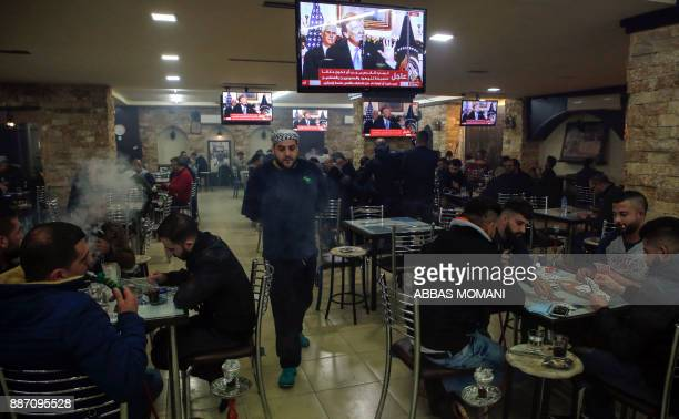 TOPSHOT Palestinians sit in a cafe in the West Bank city of Ramallah on December 6 as TV screens show US President Donald Trump giving a speech in...
