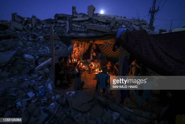 Palestinians sit in a tent that has been set up at the ruins of a building destroyed in recent Israeli air strikes, in Beit Lahia in the northern...