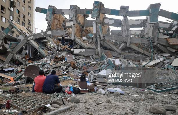 Palestinians sit in front of a building destroyed by an Israeli air strike, in Gaza City on May 21 after a ceasefire has been agreed between Israel...
