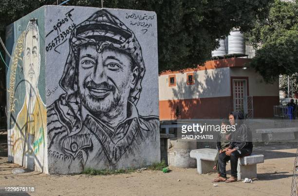 Palestinians sit next to a graffiti depicting late Palestinian leader Yasser Arafat in Rafah in the southern Gaza Strip on November 11 on the 16th...