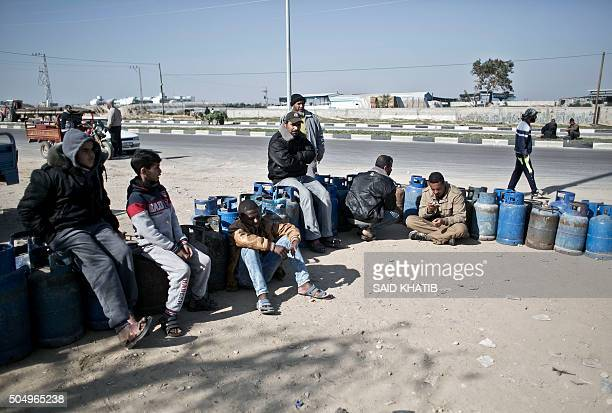 Palestinians sit next to empty cooking gas bottles as they wait to get them refilled at a fuel station in Rafah in the southern Gaza Strip on January...