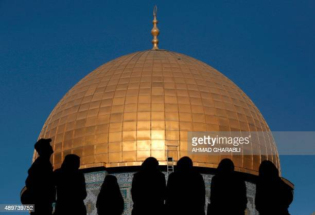 Palestinians sit on a wall overlooking the Dome of Rock mosque inside the AlAqsa Mosque compound Islam's third holiest site following the morning Eid...