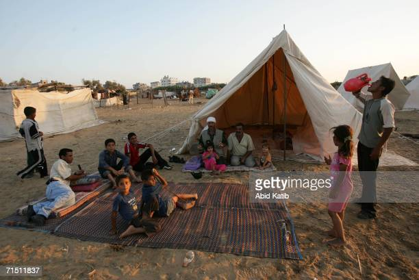 Palestinians sit outside near the tent at a refugee camp built by United Nations as a makeshift where the Palestinian families can take a refuge on...