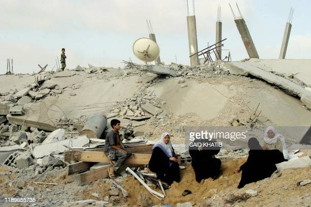Palestinians sit over the rubble of their homes demolished by the Israeli army at the Rafah refugee camp in the southern Gaza Strip 29 July 2004....