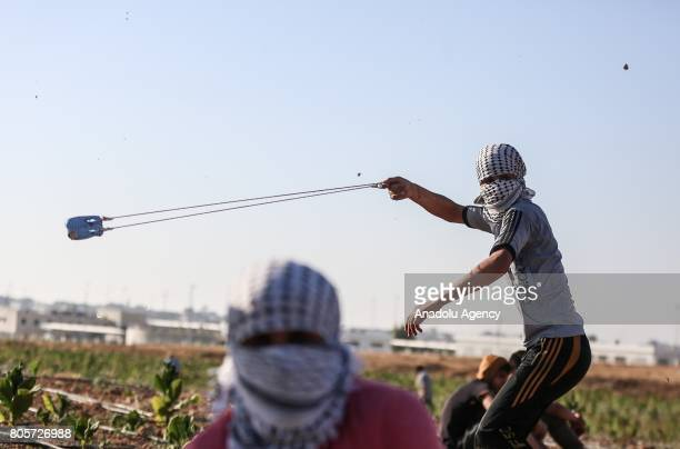 Palestinians sling stones as a respond to Israeli security forces' intervention during a protest against the Israeli blockade at Israeli border in...