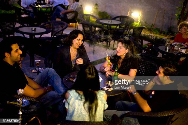 Palestinians smoke a water pipe in a coffee shop on July 20 2010 in Ramallah WestBank