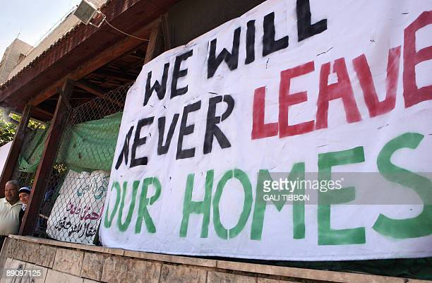 """Palestinians stand at the entrance of their home next to a placard that reads in English """"We will never leave our homes"""" during a protest against the..."""