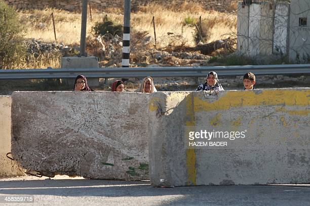 Palestinians stand behind concrete blocks at the northern main entrance of Hebron on July 2 as Israeli troops locked down the occupied West Bank city...
