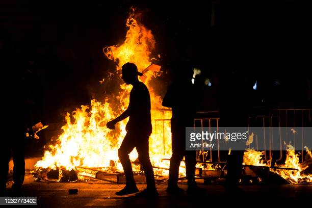 Palestinians stand next to a burning barricade during clashes with Israeli police officers during the holy month of Ramadan on May 8, 2021 in...