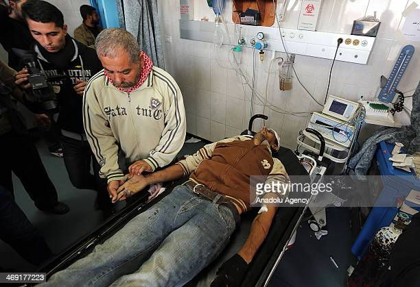 Palestinians stand next to the body of Ibrahim Mansour shot dead in the head by Israeli forces at a local hospital in Gaza City on February 13 2014 A...