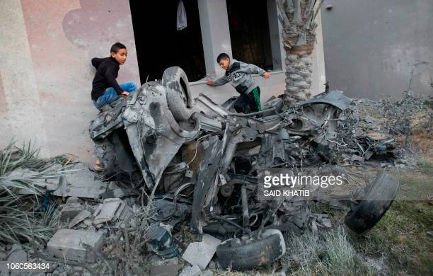 TOPSHOT Palestinians stand next to the remains of a car that was destroyed following an Israeli air strike in Khan Yunis in the southern Gaza Strip...