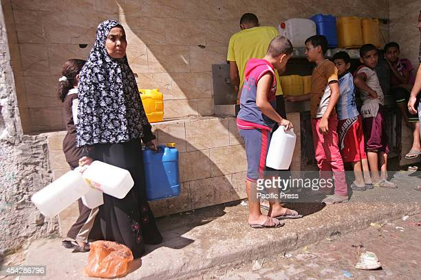 Palestinians standing in a queue to get water from a desalination plant after the war ended officially in Rafah Southern Gaza strip