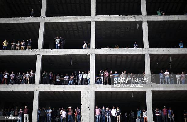 Palestinians standing on a building under construction look at security forces during an anti-Israel on November 13, 2013 in the streets of Gaza City...