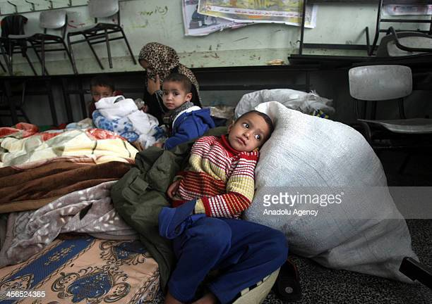 Palestinians stay in a school after being evacuated from their houses that are flooded with rainwater on a stormy day in Khan Younis in the southern...