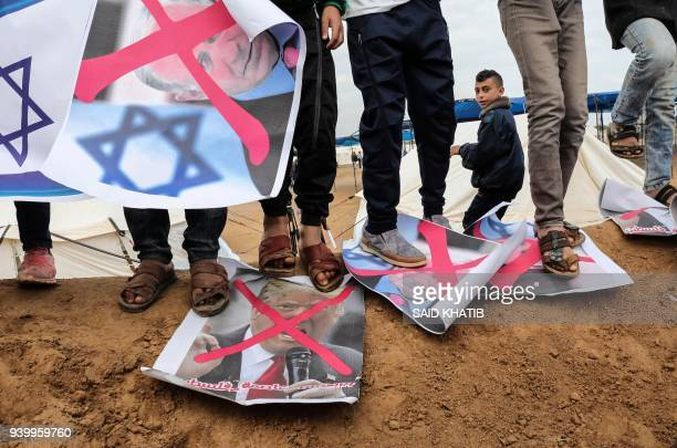 Palestinians step on crossedout posters depicting Israeli Prime Minister Benjamin Netanyahu and US President Donald Trump during a tent city protest...