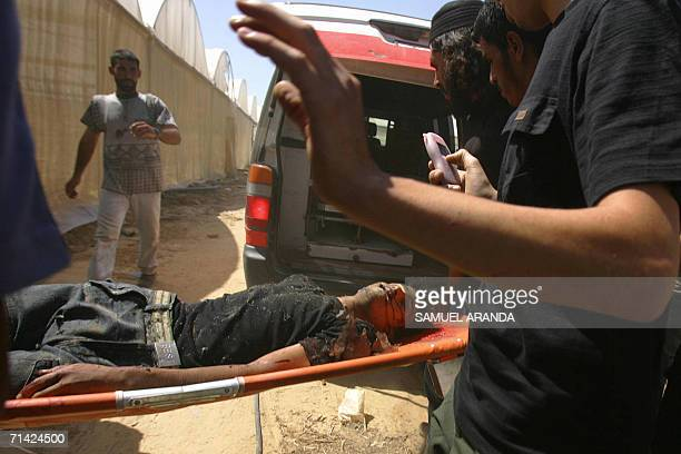 Palestinians stretcher away the body of a man killed during an Israeli air strike north of the town of Khan Yunis in the Gaza Strip 12 July 2006 At...