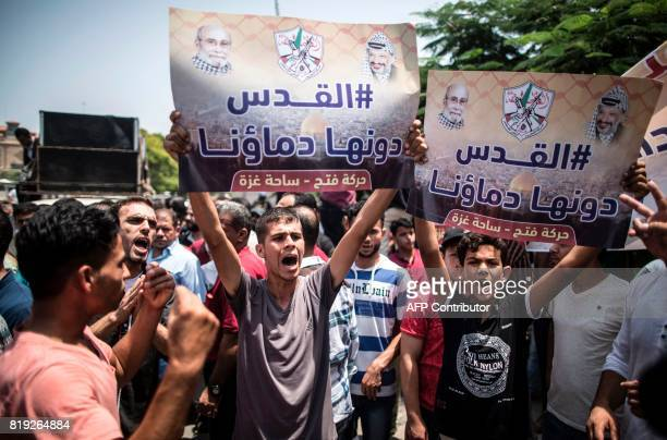 TOPSHOT Palestinians Supporters of Fateh movement hold banners and march during a demonstration in Gaza City on July 20 2017 against new Israeli...