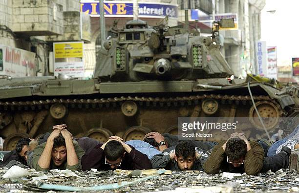 Palestinians surrender to Israeli soldiers March 30 2002 during the occupation of the West Bank town of Ramallah The Israeli army is in the process...