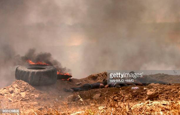 TOPSHOT Palestinians take cover from shots during clashes with Israeli forces near the border between the Gaza strip and Israel east of Gaza City on...