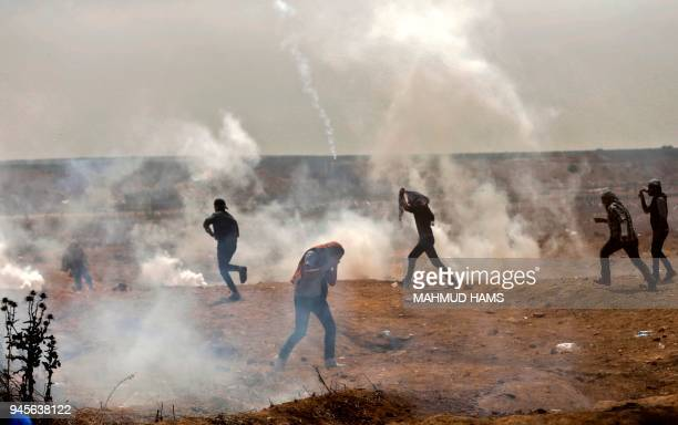 TOPSHOT Palestinians take cover from tear gas smoke during clashes with Israeli security forces near the border fence with Israel east of Gaza City...