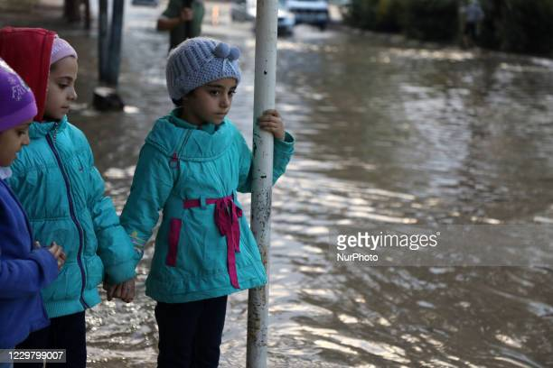 Palestinians they cross through flood waters following heavy rains in Gaza City on November 26 2020
