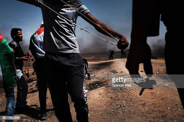 Palestinians throw a rocks towards the border fence with Israel as mass demonstrations at the fence continue on May 11 2018 in Gaza City Gaza One man...