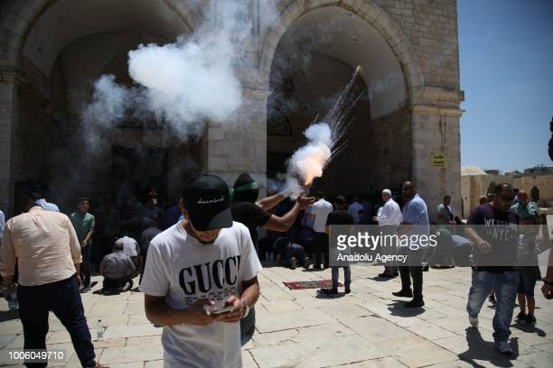 Palestinians throw fireworks in response to Israeli police officers after they attacked Palestinians with tear gas canisters and and blast bombs...