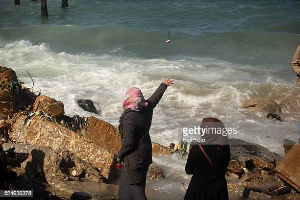 Palestinians throw flowers into the sea in remembrance of the Chapel Hill shooting victims in Gaza City February 14 2015 Three young Muslims were...