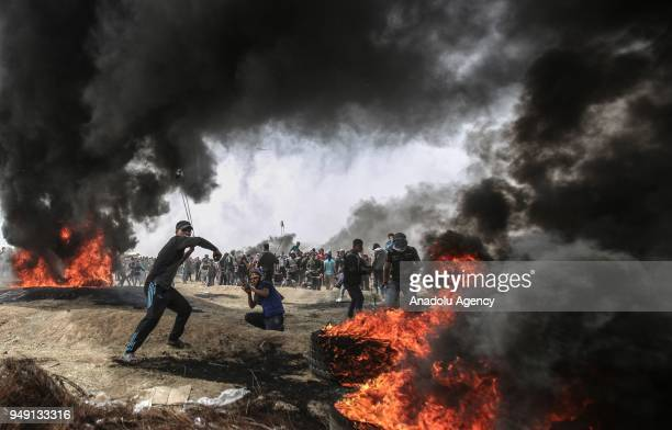 Palestinians throw rocks as they set tires on fire in response to Israel's intervention during Great March of Return demonstration near GazaIsrael...