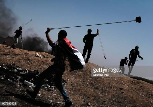 Palestinians throw rocks toward the border fence with Israel as mass demonstrations at the fence continue on May 11 2018 in Gaza City Gaza One man...