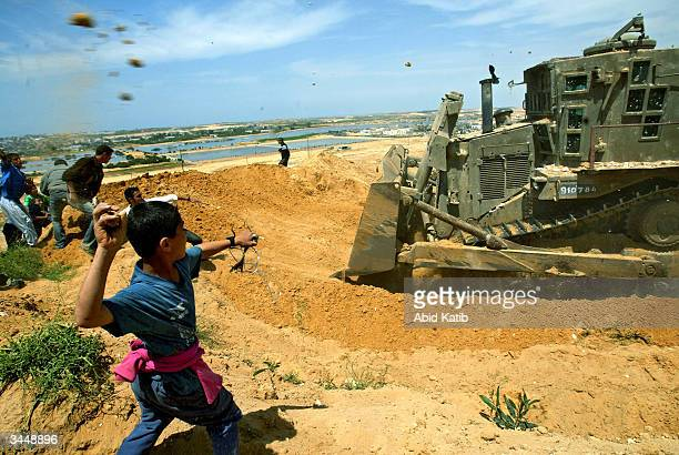 Palestinians throw rocks towards an army bulldozer during clashes with Israeli soldiers April 20 2004 near the Beit Lahyea Refugee Camp in the Gaza...