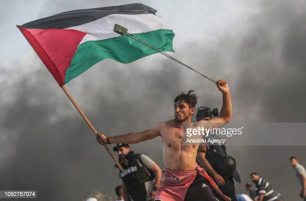 Palestinians throw stones and burn tyres in response to Israeli forces' intervention as they gather to support the maritime demonstration to break...