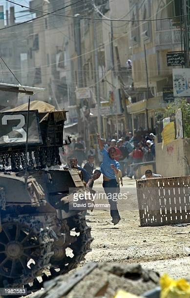 Palestinians throw stones at a tank during clashes with Israeli armored troops May 8 2003 in the Balata Refugee Camp in the West Bank town of Nablus...