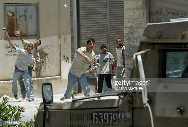Palestinians throw stones at an Israeli army vehicle in the Balata refugee camp in the northern West Bank city of Nablus 13 July 2004. Israeli Prime...