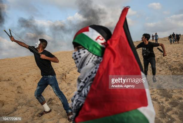 Palestinians throw stones in response to Israeli forces' intervention as they gather to support the maritime demonstration to break the Gaza blockade...