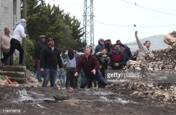 Palestinians throw stones in response to Israeli intervention during a protest against building of Jewish settlements and separation wall at Kafr...