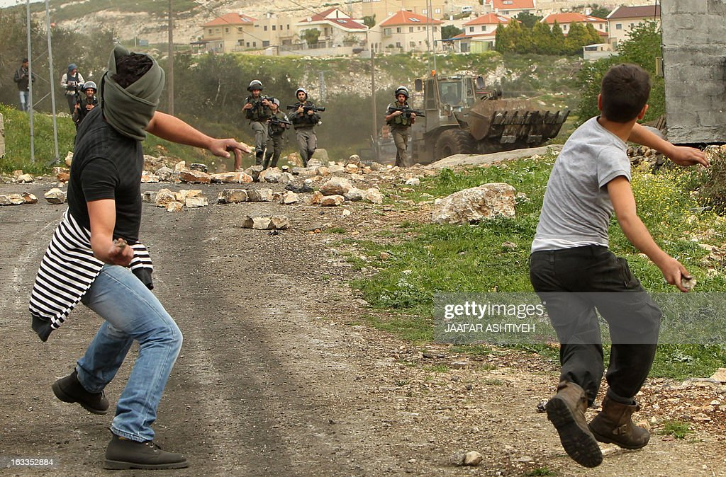 Palestinians throw stones towards Israeli border guards during clashes following a protest against the expropriation of Palestinian land by Israel on March 1, 2013, in the village of Kafr Qaddum, n...