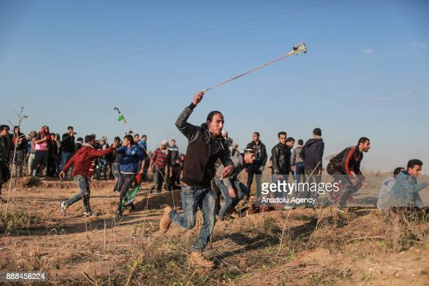 Palestinians throw stones towards Israeli security forces a demonstration against US President Donald Trump's recognition of Jerusalem as Israel's...