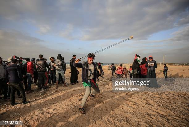 Palestinians throw stones with slingshots in response to Israeli forces' intervention with gas bombs during maritime protest against Israels ongoing...