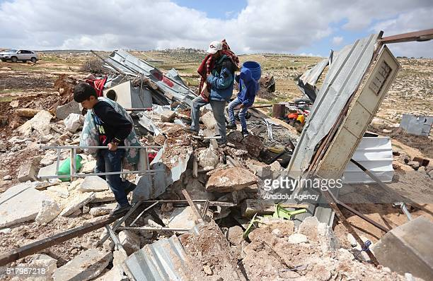 Palestinians try to collect useable household goods and belongings inside the debris of their house after Israeli authorities demolished some houses...
