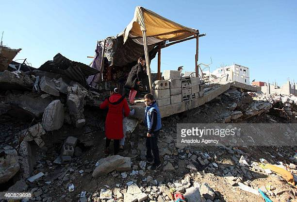 Palestinians try to live in a shanty built on the ruins of a building which were destroyed by the Israeli army's Gaza attacks and waiting to be...