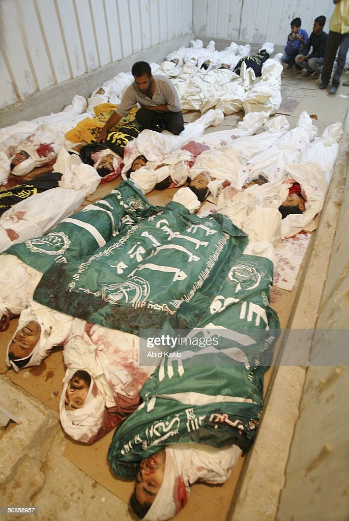 Palestinians try to recognise their relatives amongst 29 bodies stored in a vegetables and flowers freezer being used as a makeshift morgue, on May 20, 2004 in the Rafah refugee camp, southern Gaza Strip. Israel defied international fury at the killing of nearly 40 Palestinians in the Rafah refugee camp, to expand its bloodiest Gaza Strip raid in years on Thursday.