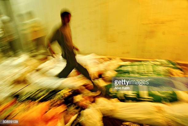 Palestinians try to recognise their relatives amongst 29 bodies stored in a vegetables and flowers freezer being used as a makeshift morgue on May 20...