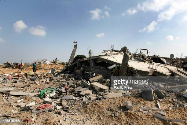Palestinians try to salvage their belongings from the rubble and debris of destroyed buildings in Rafah, in the Southern Gaza Strip during the...