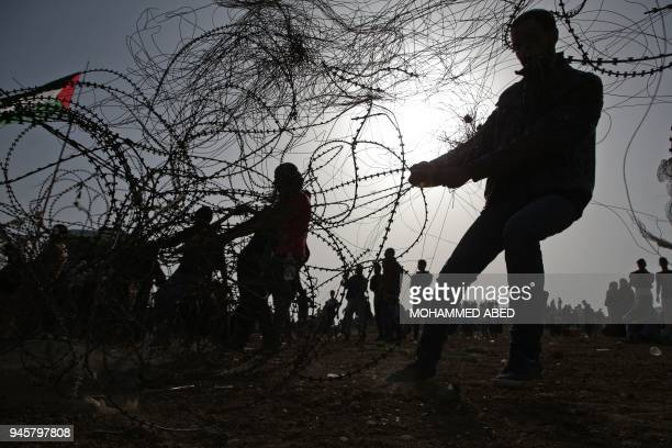 Palestinians try to take down a section of barbed wire at the border fence with Israel, east of Jabalia in the central Gaza city, during a protest on...