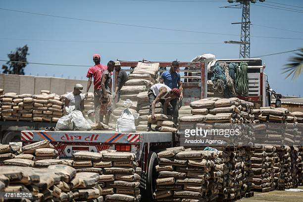 Palestinians unload bags of cement from a truck that entered Gaza from the Rafah border crossing on the border between Egypt's Sinai and the Gaza...