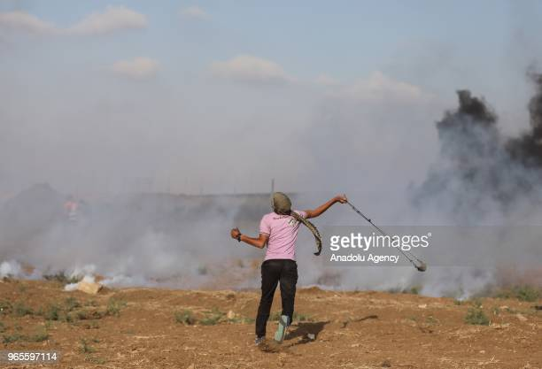 Palestinians use sling shots to throw stones as they clash with Israeli security forces along the GazaIsrael security fence during From Gaza to Haifa...